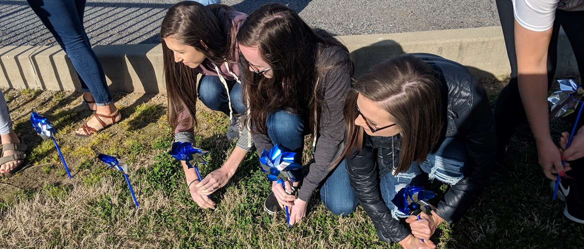 Seniors Mollie Henderson, Megan Quillen, and Abbi Jewell place blue pinwheels into the ground in support of child abuse prevention.